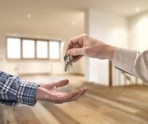 Un agent immobilier transmet des clés de maison à un acheteur